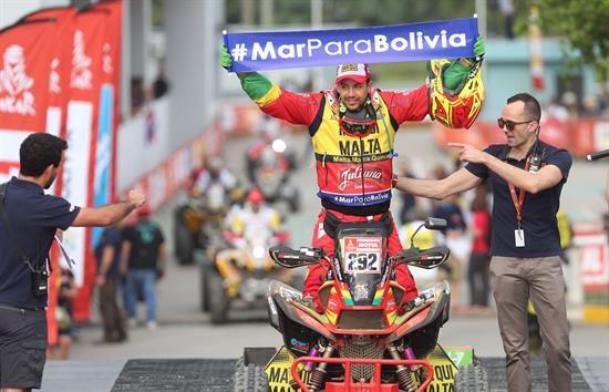 Piloto boliviano Hernán Paredes muestra cartel de Mar para Bolivia en el Dakar